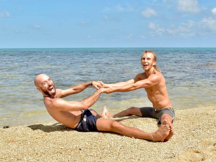 partner yoga on the beach doing yoga teacher training